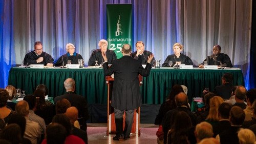 Gregory Garre '87 standing at a podium in front of a panel of distinguished alumni jurists