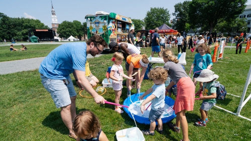 Several families make giant bubbles at one of the several children's activity stations run by Hanover Parks and Recreation.  (Photo by Eli Burakian '00)