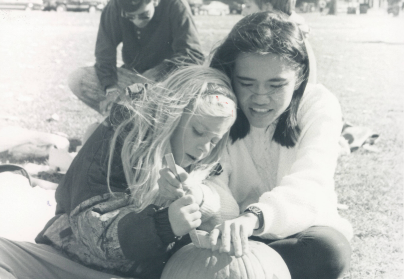 """Melissa Nguyen '95 carving a pumpkin with her """"little sister"""""""